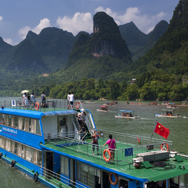 """Yangshuo, China - August 1, 2012: People in a boat cruising in the Li River and looking at the the tall limestone mountains near Yangshuo in China, Asia."" stock image"