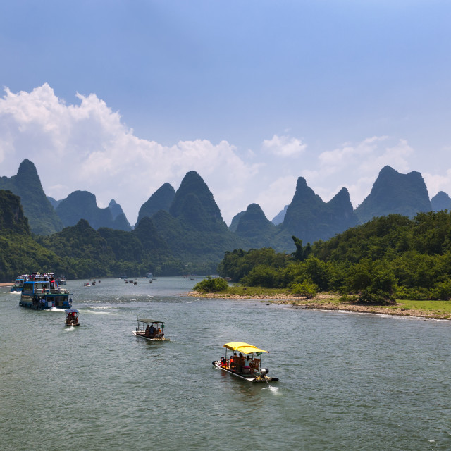 """Yangshuo, China - August 1, 2012: Boats with tourists cruising in the Li River with the tall limestone peaks in the background near Yangshuo in China, Asia."" stock image"