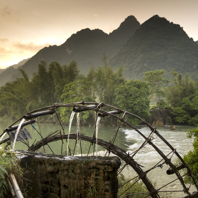 """""""Bamboo water wheel gets water from the river to irrigate rice fields"""" stock image"""