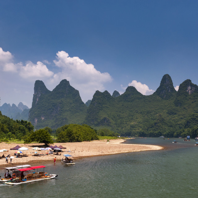 """Yangshuo, China - August 1, 2012: Boats and rafts with tourists cruising in the Li River with the tall limestone peaks in the background near Yangshuo in China, Asia."" stock image"