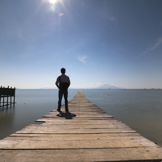 """A man stands on a wooden bridge and is watching the beauty of the sea. The concept of loneliness"" stock image"