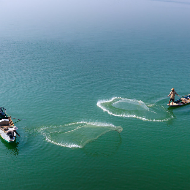 """Two men cast their nets fishing on the Tri An reservoir"" stock image"