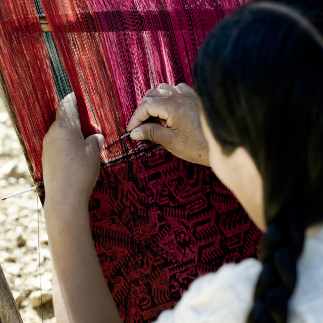 """Native Peruvian woman weaving intricate llama wool garments using a traditional hand loom"" stock image"