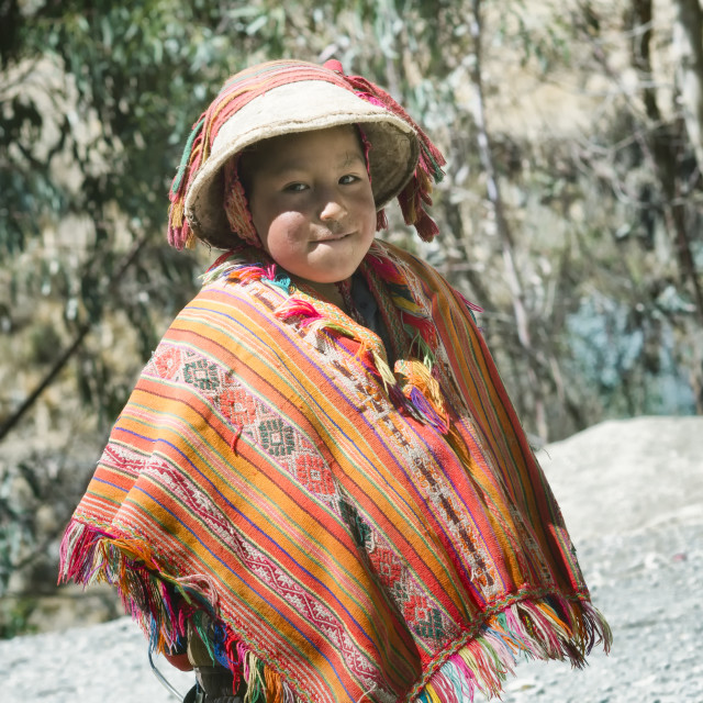 """Smiling native peruvian boy wearing colorful handmade traditional poncho and a hat"" stock image"
