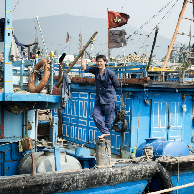 """""""Smiling fisherman standing on his boat"""" stock image"""