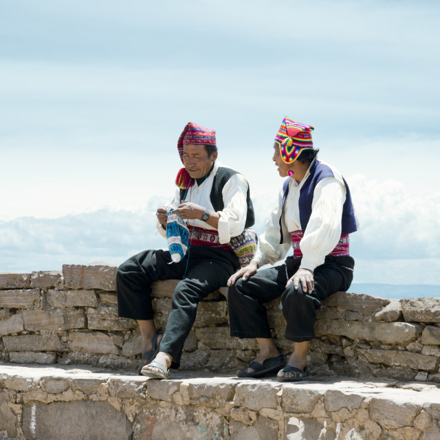 """Two men dressed in traditional outfits specific for the Taquile Island region, one of them knitting a hat"" stock image"