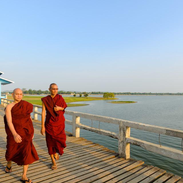 """MANDALAY, MYANMAR - 3 JUN 2014: Two buddhist monks walk on the U-Bein..."" stock image"