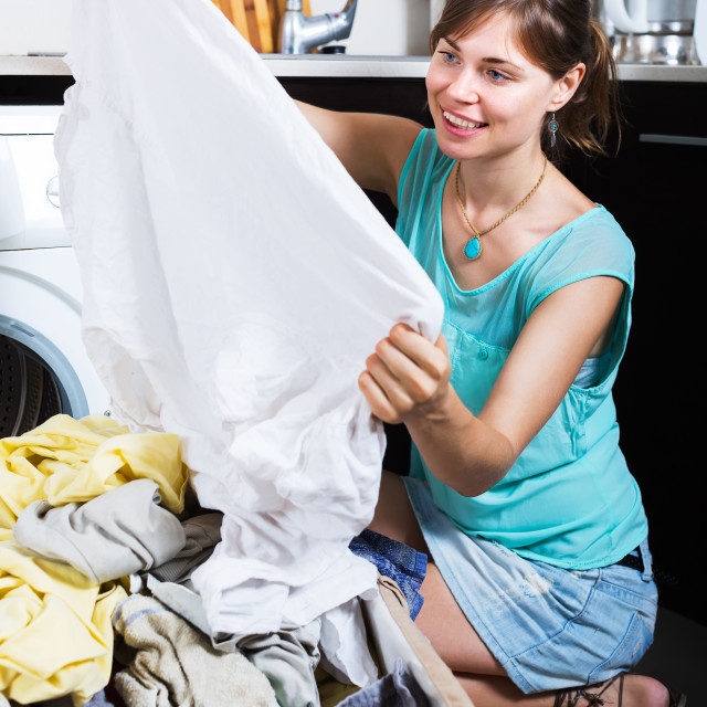 """""""Woman enjoying clean clothes after laundry"""" stock image"""