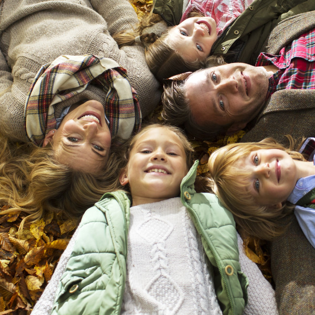 """""""Family lying down on Autumn leaves"""" stock image"""