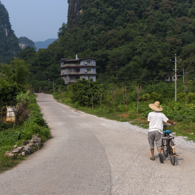 """Yangshuo, China - August 2, 2012: Man with a bicycle in a contry road near the town of Yangshuo in China, Asia, with the tall limestone peaks on the background"" stock image"