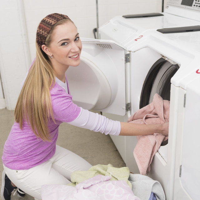 """Woman loading laundry into washing machine"" stock image"