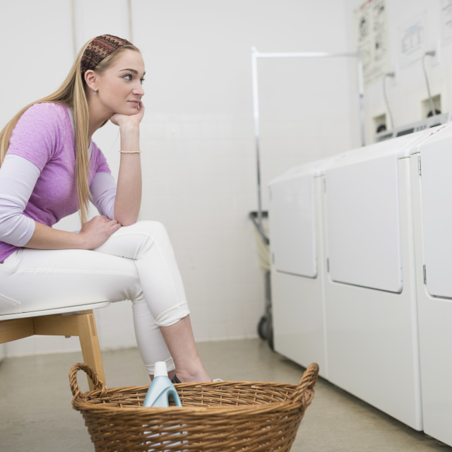 """""""Woman waiting in laundromat"""" stock image"""