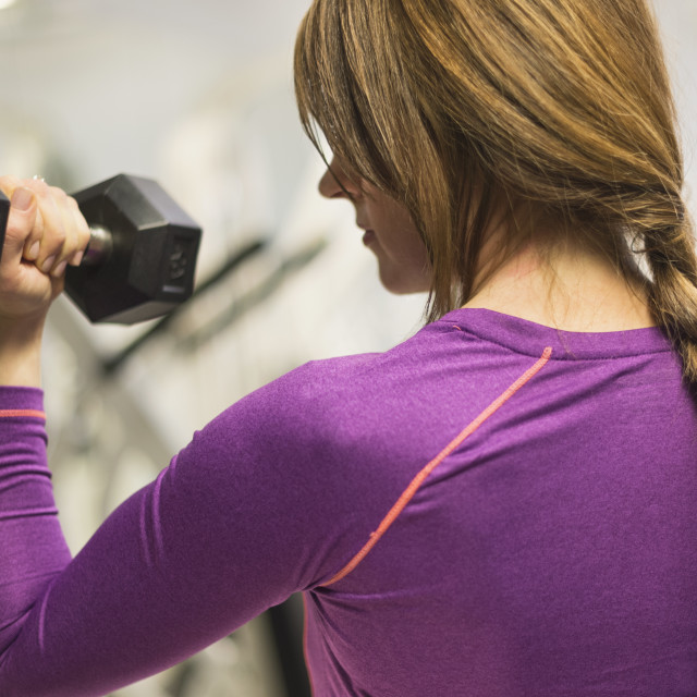 """Portrait of woman weightlifting"" stock image"