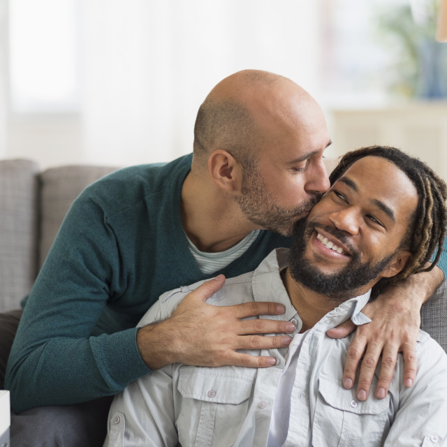 """""""Homosexual couple kissing by sofa in living room"""" stock image"""
