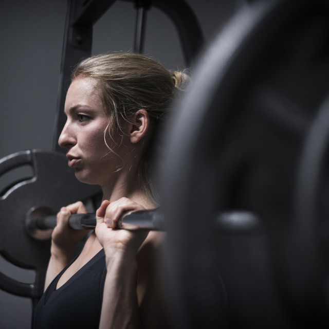 """Young woman weightlifting in gym"" stock image"