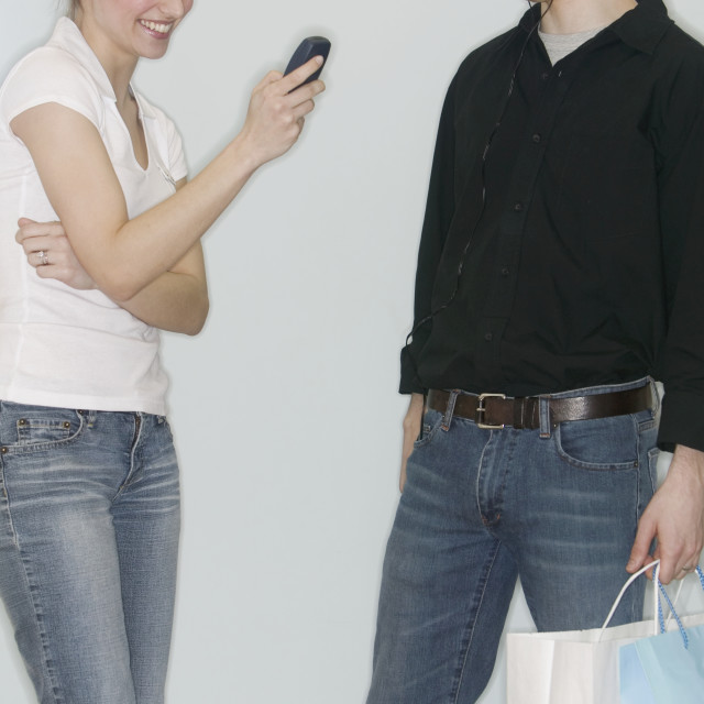 """Couple with personal stereo and mobile phone"" stock image"
