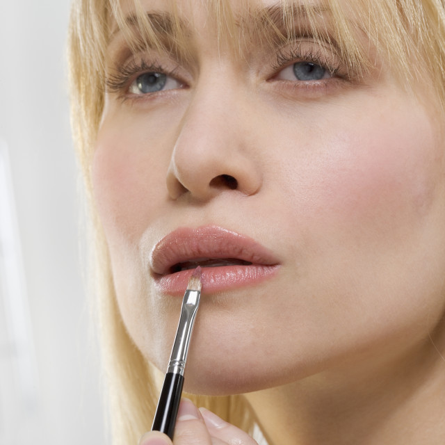"""Woman applying lipstick with brush"" stock image"
