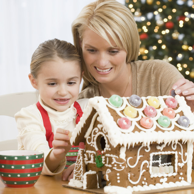 """""""Mother and daughter making gingerbread house"""" stock image"""