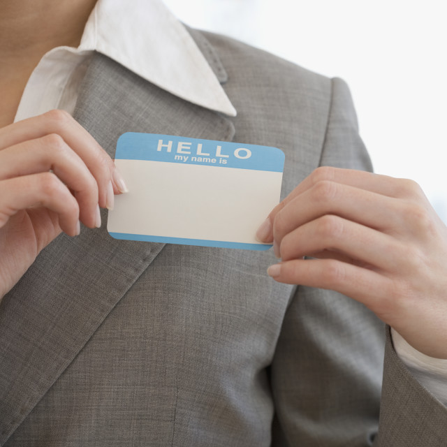 """Businesswoman putting on Hello My Name Is sticker"" stock image"