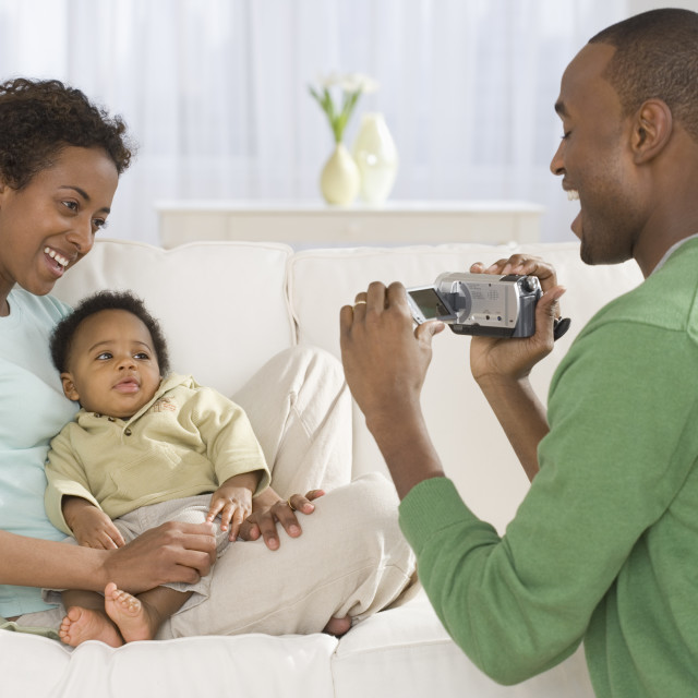 """Father video recording mother and baby on sofa"" stock image"