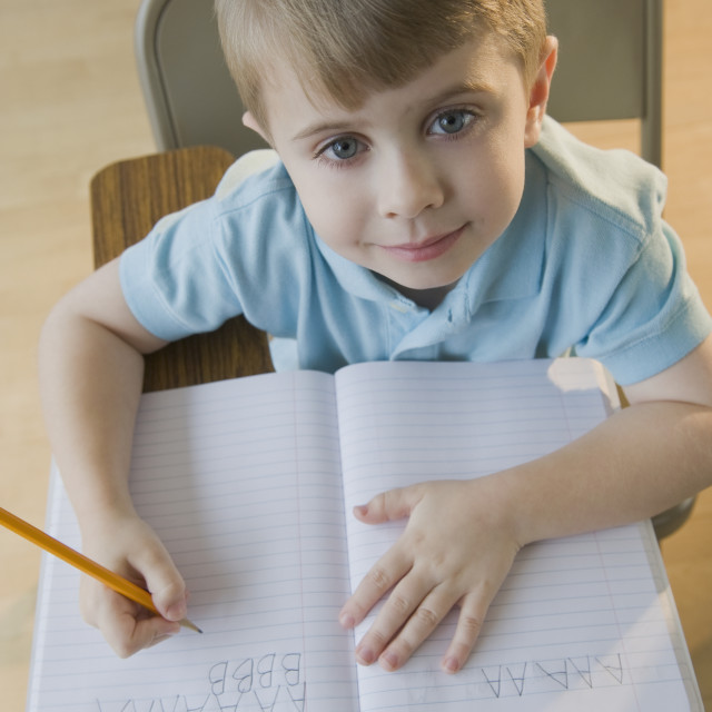 """Boy writing letters in classroom"" stock image"