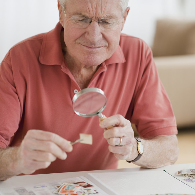 """Senior man looking at stamp collection"" stock image"