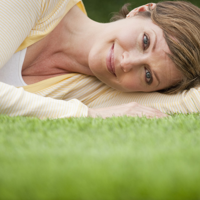 """Contented woman lying on grass"" stock image"