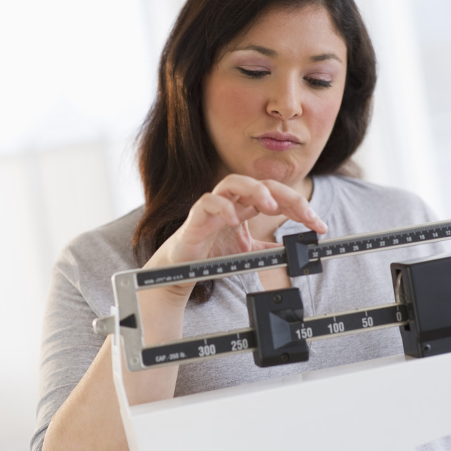 """""""Disappointed woman standing on scale"""" stock image"""