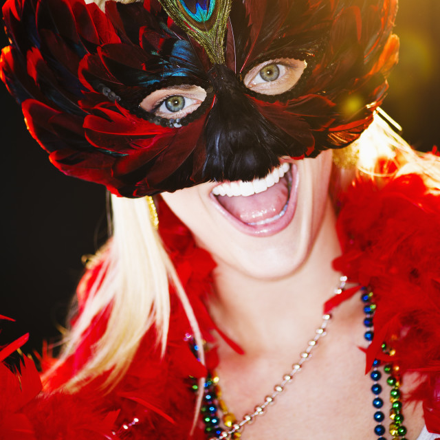 """Person wearing a mardi grass mask and beads"" stock image"