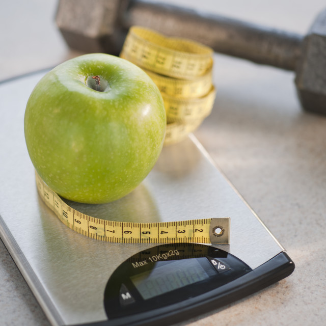 """""""Green apple on weight scale, tape measure and exercise weight in background"""" stock image"""