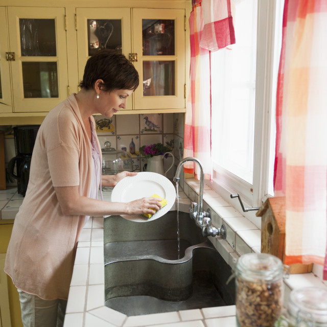 """Woman washing dishes in domestic kitchen"" stock image"