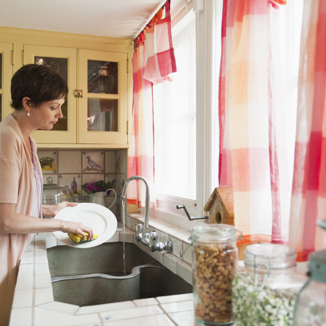 """Woman washing dishes"" stock image"