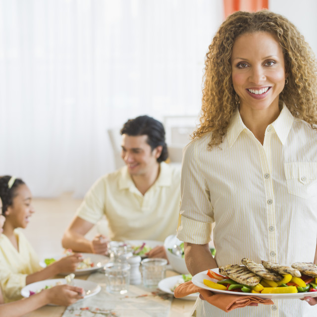 """""""Woman holding dinner plate, with husband and daughters (10-13) in background"""" stock image"""