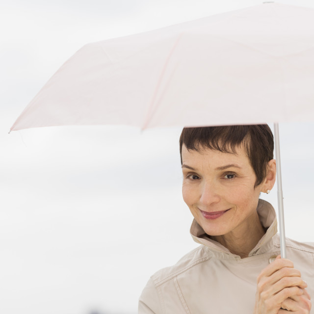 """""""Portrait of smiling woman wearing raincoat and holding umbrella"""" stock image"""
