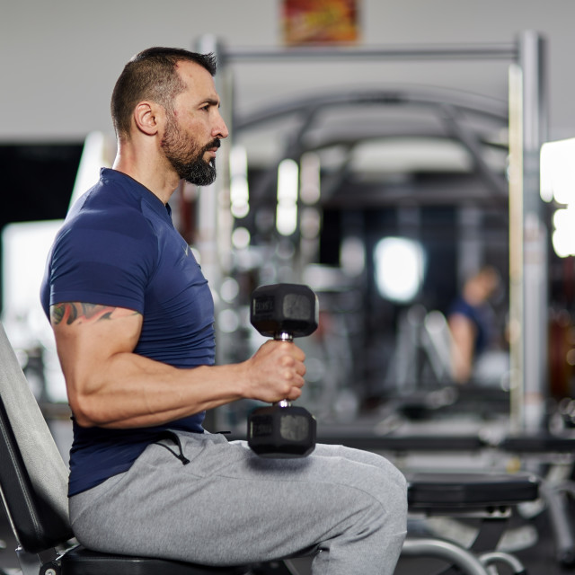"""""""Man doing biceps curl in the gym"""" stock image"""