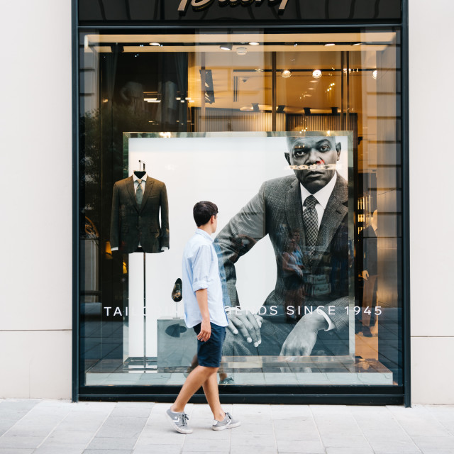 """Young man in front of luxury fashion storefront"" stock image"