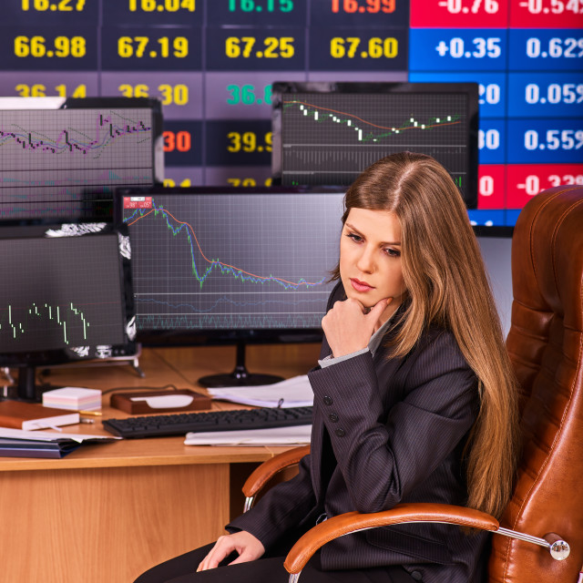 """""""Stock exchange people. Trader woman sitting table surrounded by monitors."""" stock image"""