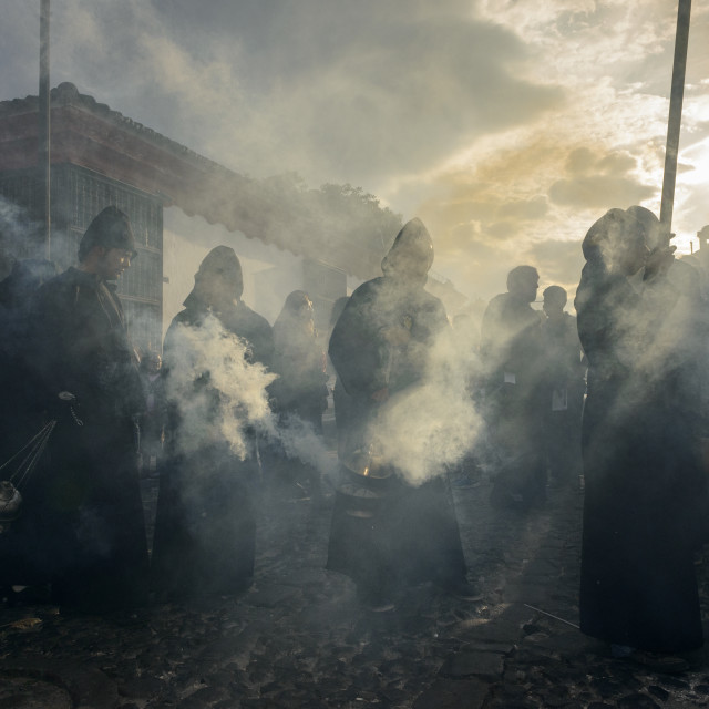"""""""Antigua, Guatemala - April 19, 2014: Silhouette of men wearing black robes and hoods spreading incense in a street of the city of Antigua during a procession of the Holy Week in Antigua, Guatemala"""" stock image"""