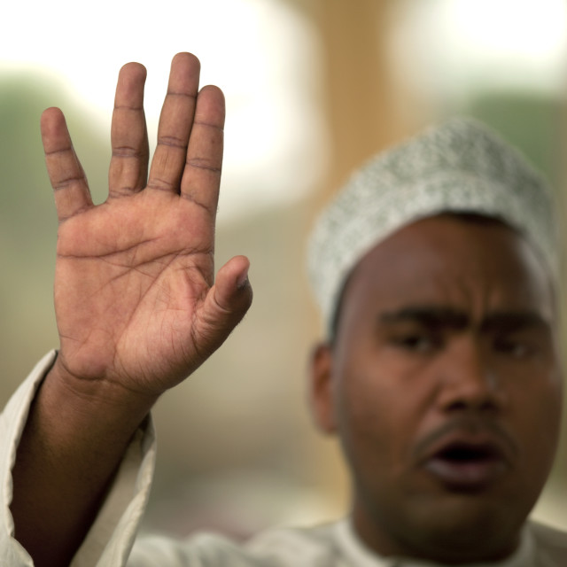 """Man Waving Hand In Nizwa Cattle Market, Nizwa, Oman"" stock image"