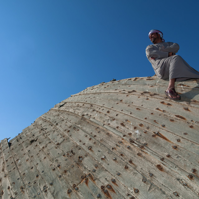 """Man Sitting On The Wreck Of Dhow And Looking Proudly, Masirah Island, Oman"" stock image"