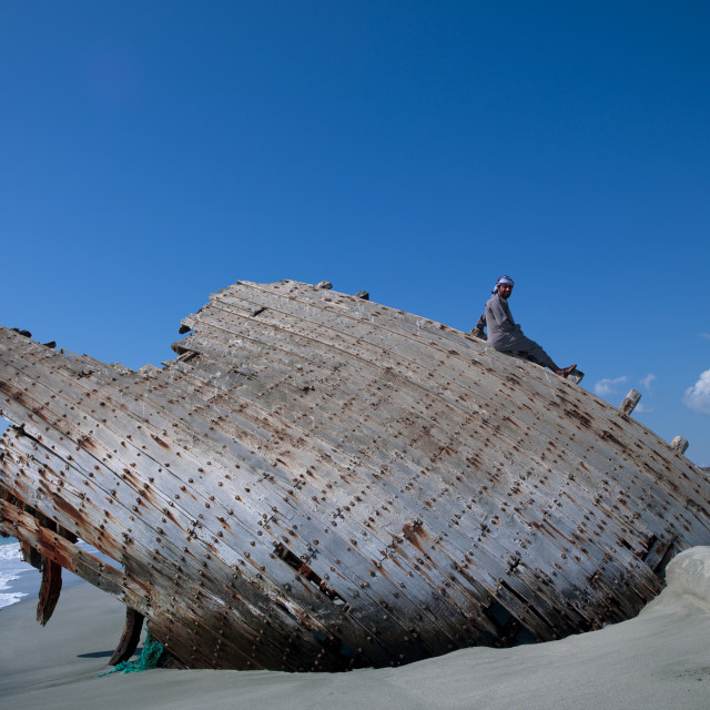 """Man Sitting On The Wreck Of Dhow On The Beache, Masirah Island, Oman"" stock image"