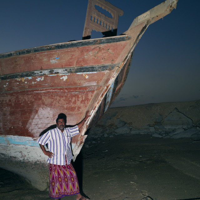 """Man Standing Beside The Dhow In Masirah Island, Oman"" stock image"