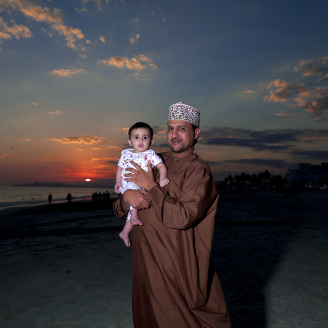 """Man Holding His Baby Standing On The Beach At Dusk, Salalah, Oman"" stock image"