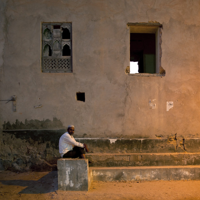"""Man Sitting On Stairs Of An Old Building, Salalah, Oman"" stock image"
