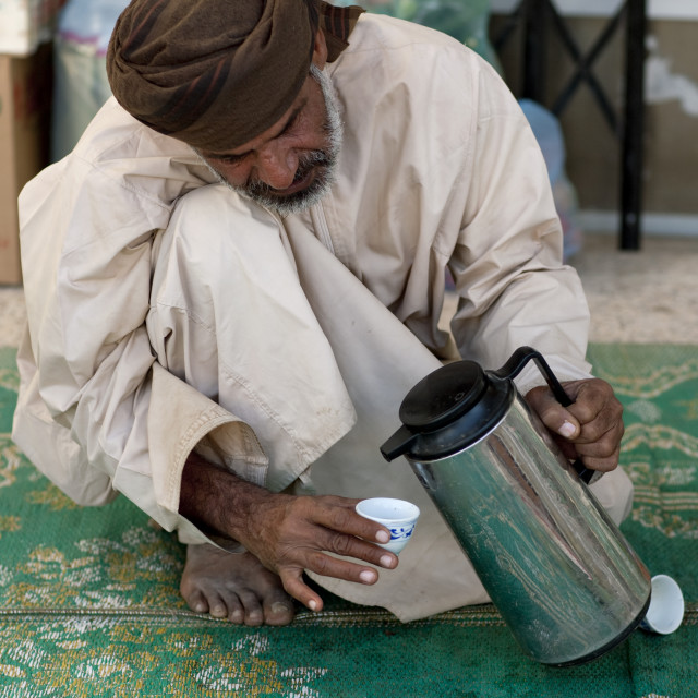 """Man Squatting For Serving Coffee, Sinaw, Oman"" stock image"