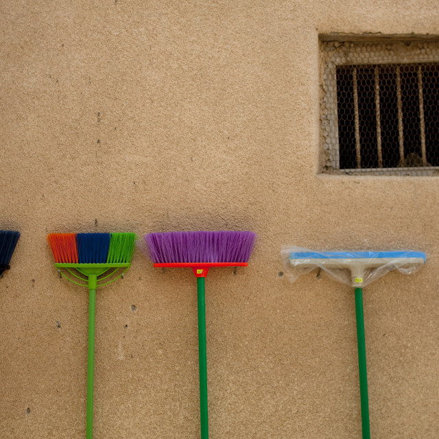 """""""Brooms In Different Colors Leaned On The Wall Of Muscat Muttrah Souk, Oman"""" stock image"""