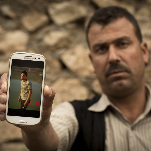 """Yezedi Refugee From Sinjar Showing The Picture Of His Dead Relative Killed By..."" stock image"