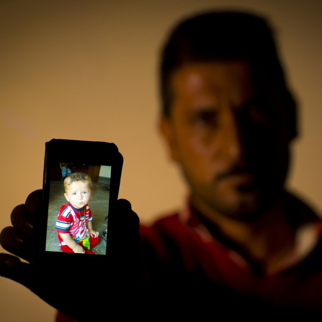 """Yezedi Refugee From Sinjar Showing A Relative Killed By Daesh On His Mobile..."" stock image"