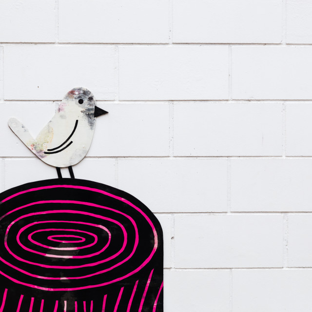 """White bird perched on a black and pink tree stump"" stock image"