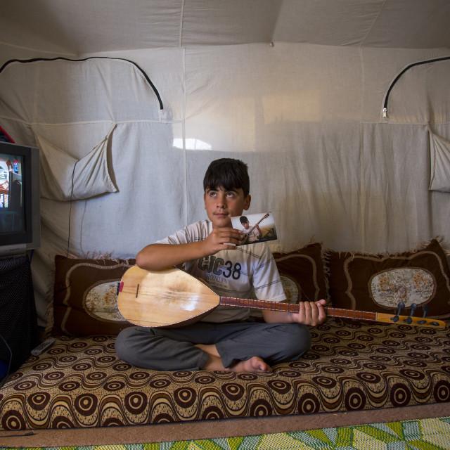 """Dylan, A Blind Syrian Refugee Playing Saz In Qushtapa Refugee Camp, Erbil"" stock image"